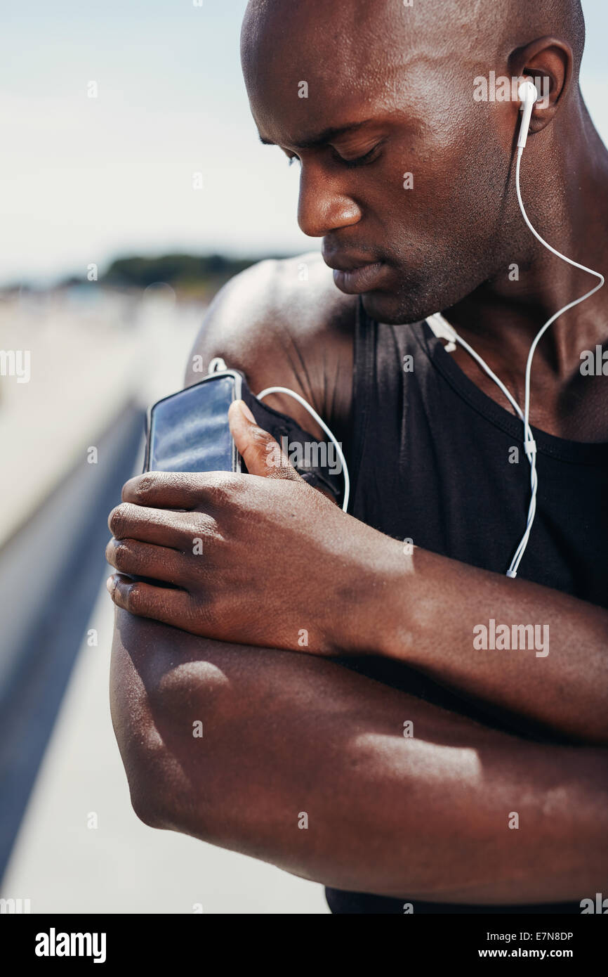 African muscular athlete listening to music. Male model listening to music from his mobile phone on armband. - Stock Image