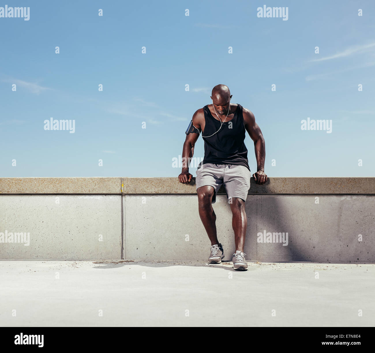 Muscular young man taking breath after his run. African male athlete outdoors with copy space. Male runner relaxing - Stock Image