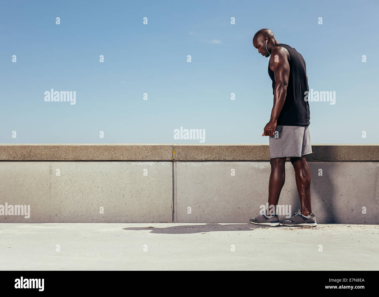 Image muscular young man on a walkway getting ready for his run. Focused male athlete preparing for his running - Stock Image