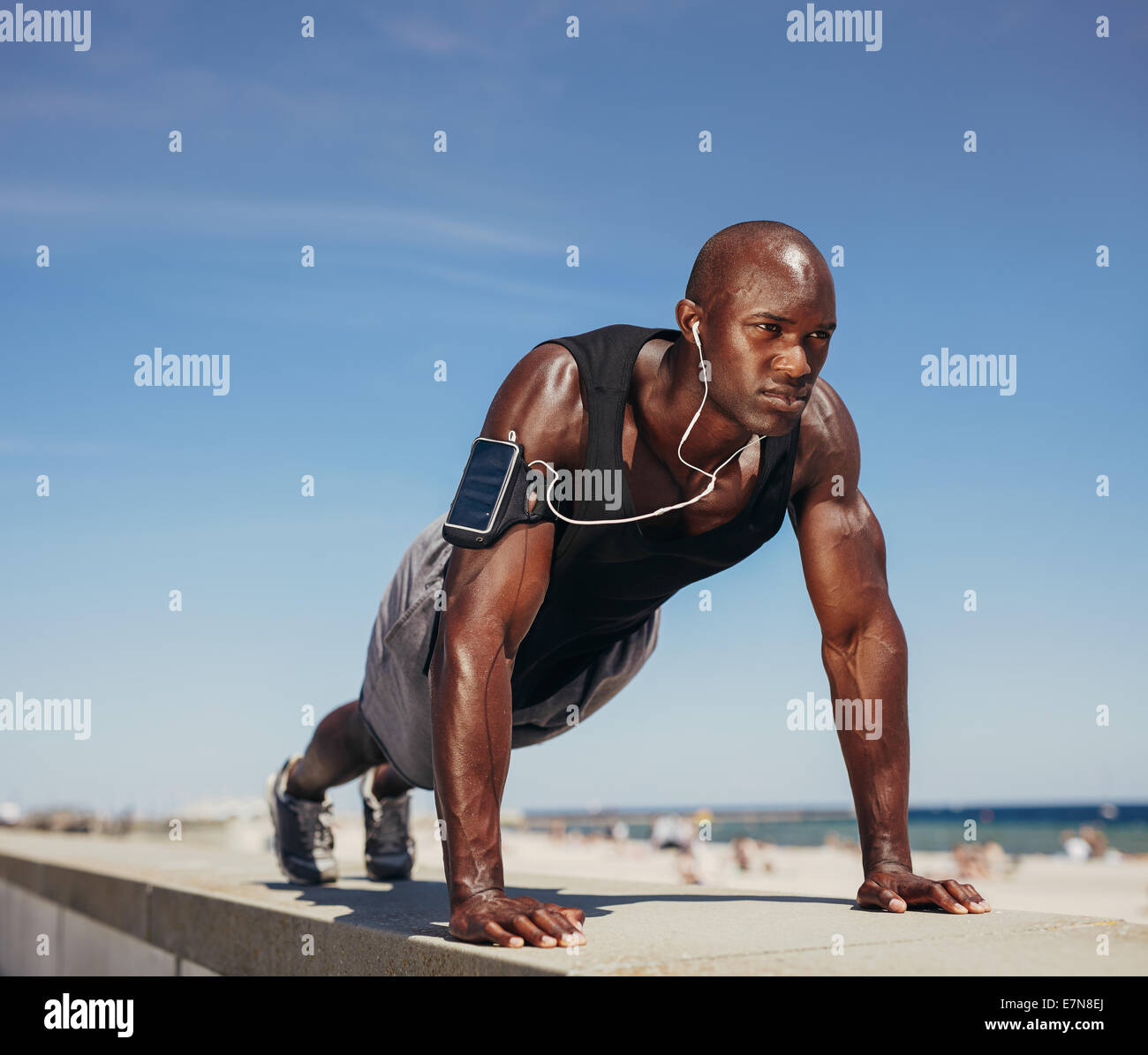 Muscular man doing push ups against blue sky. Strong male athlete working out outdoors. - Stock Image