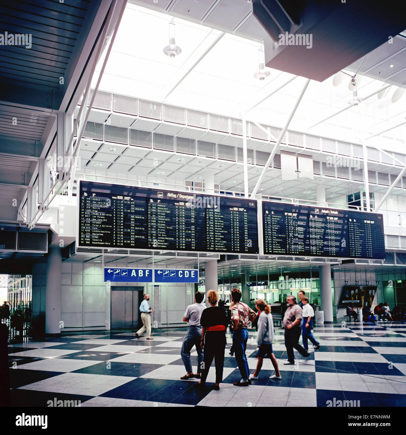 Travellers and departures and arrivals boards Franz-Joseph Strauss airport Munich Bavaria Germany Europe - Stock Image