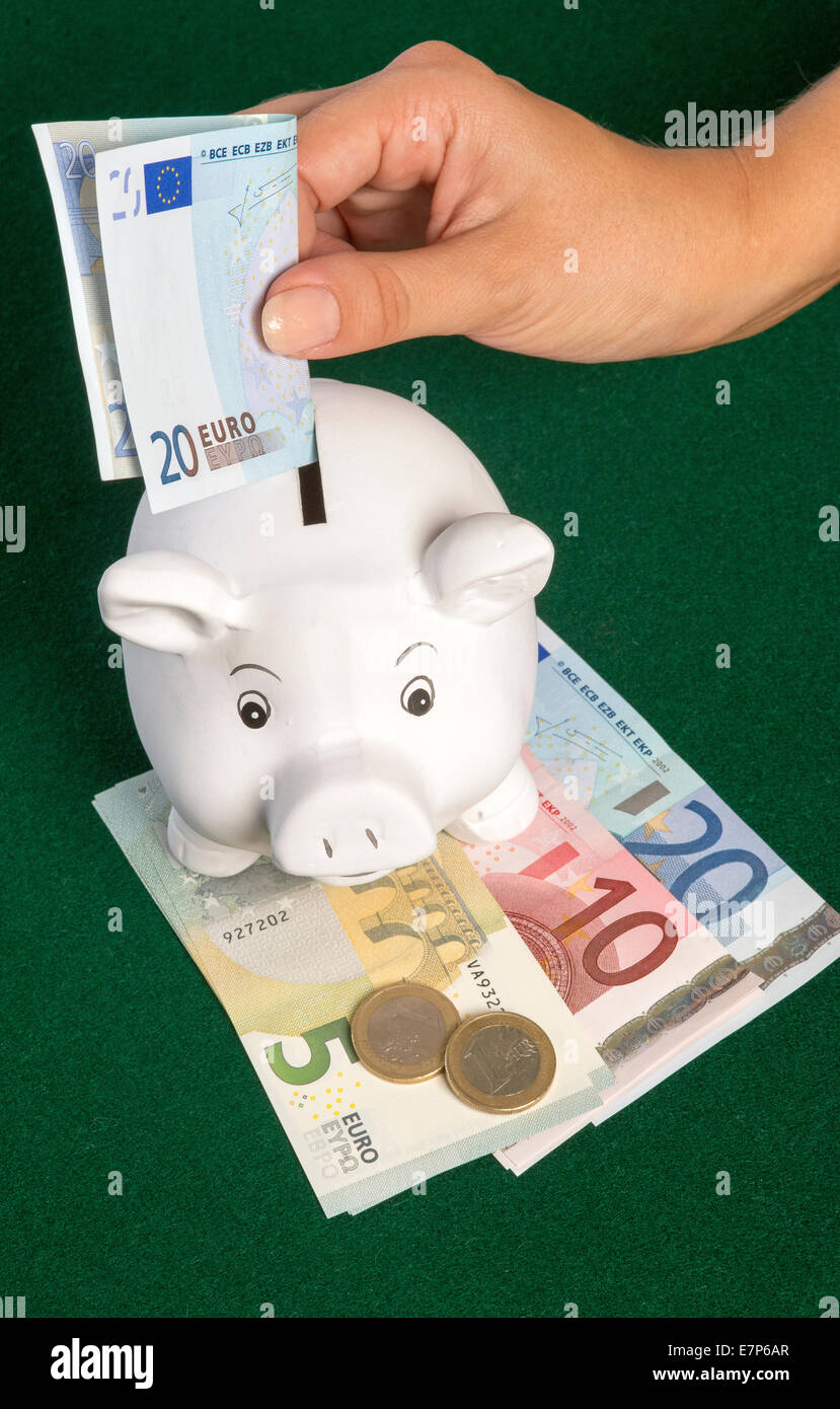 Euros and a piggy bank money box A twenty Euro banknote being placed into slot - Stock Image
