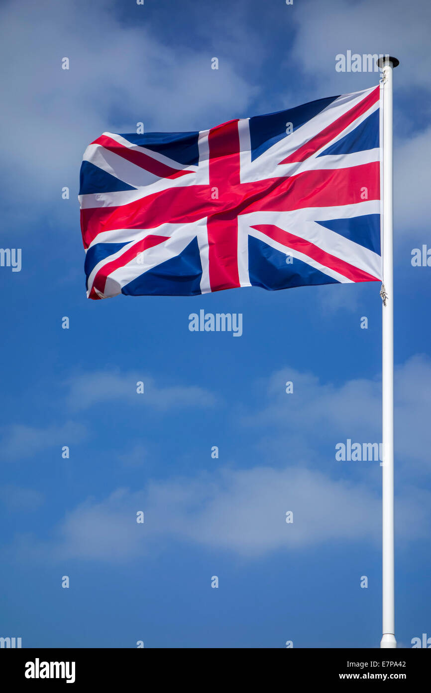 Union Jack / national flag of the United Kingdom on flagpole flying in the wind against cloudy sky - Stock Image