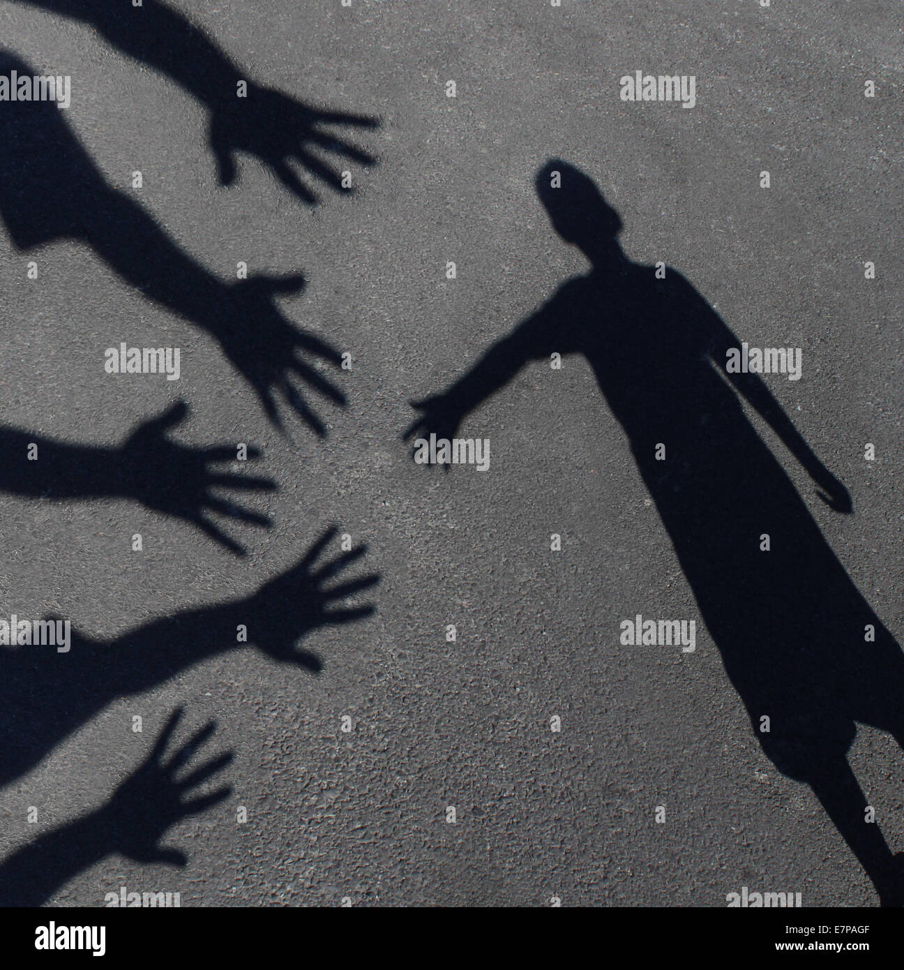 Community support and helping  children concept with shadows of a group of extended adult hands offering help or - Stock Image