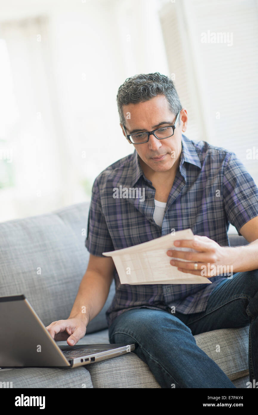 Man doing home finances with laptop - Stock Image