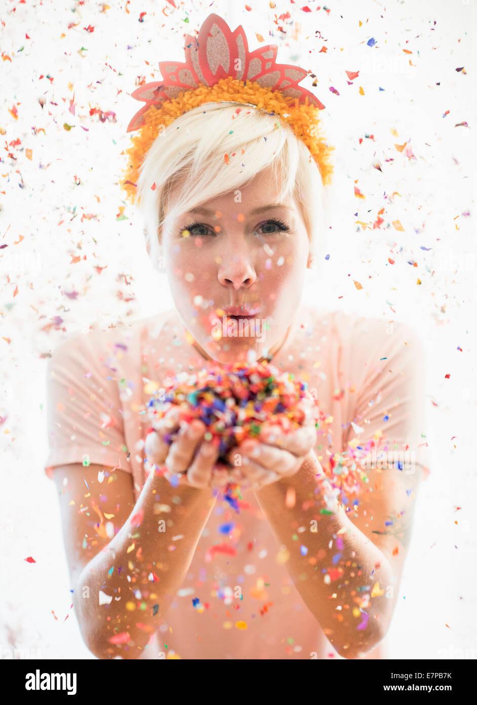 Woman wearing tiara blowing confetti - Stock Image