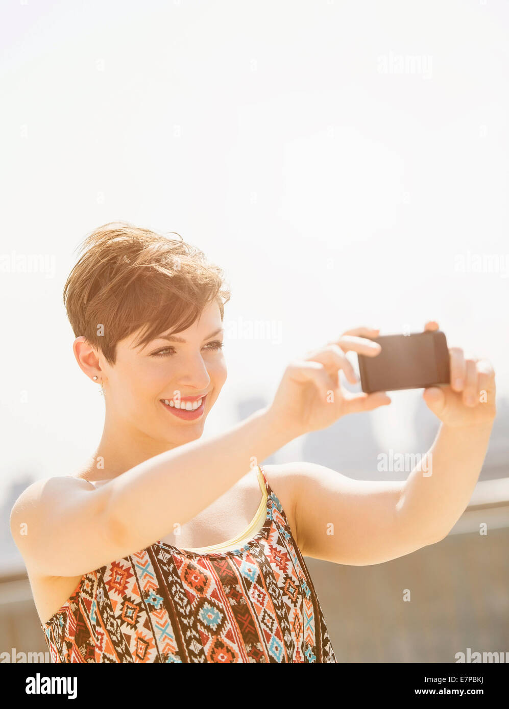 Young woman taking selfie with mobile phone - Stock Image