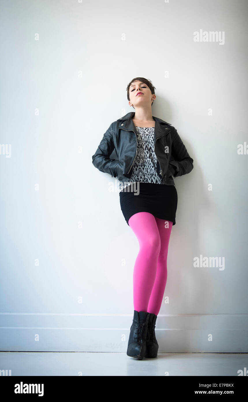 Woman wearing leather jacket, mini skirt and ping tights - Stock Image
