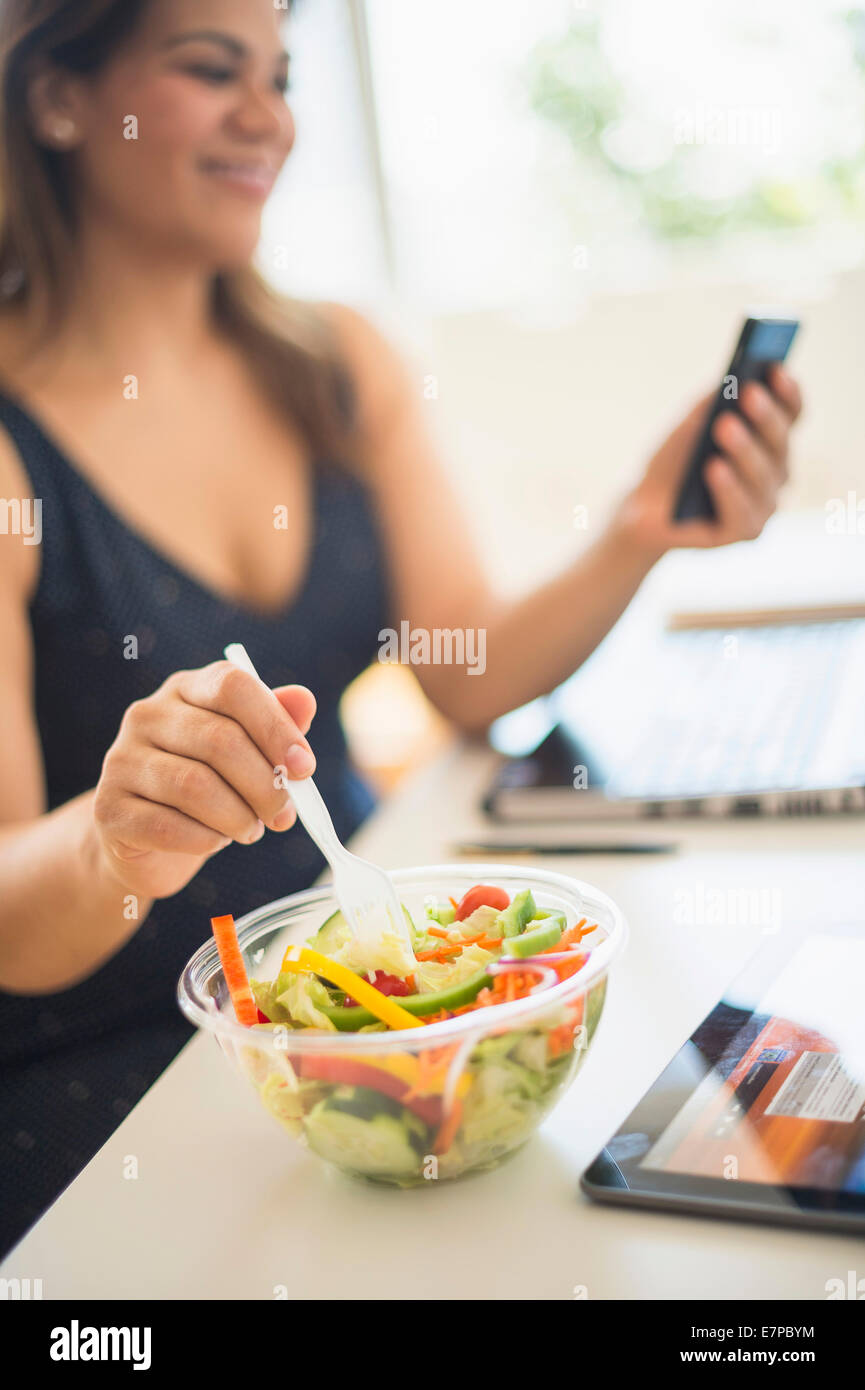 Woman eating salad and using mobile phone in office - Stock Image