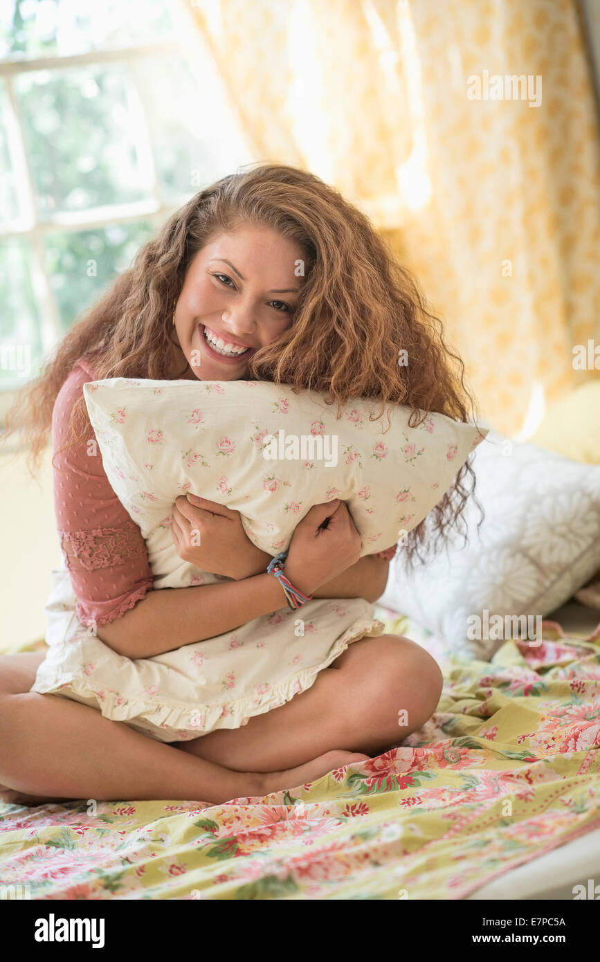 Portrait of woman embracing pillow Stock Photo