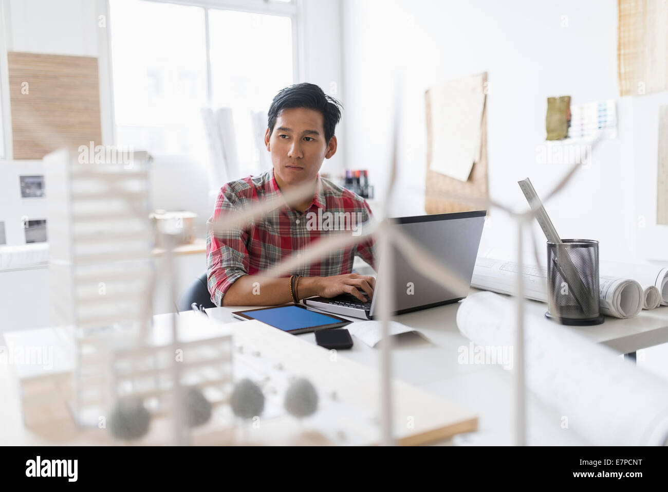 Wind turbine models on desk in front of architect - Stock Image