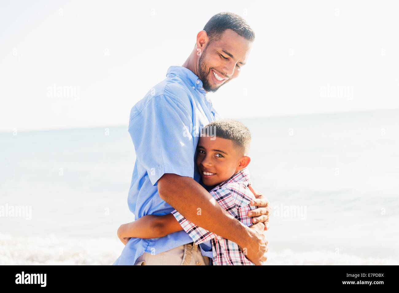 Father and son (10-11) embracing on beach - Stock Image
