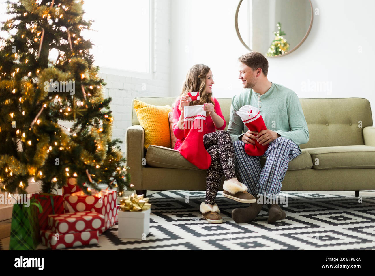 Young couple with Christmas stockings on sofa Stock Photo