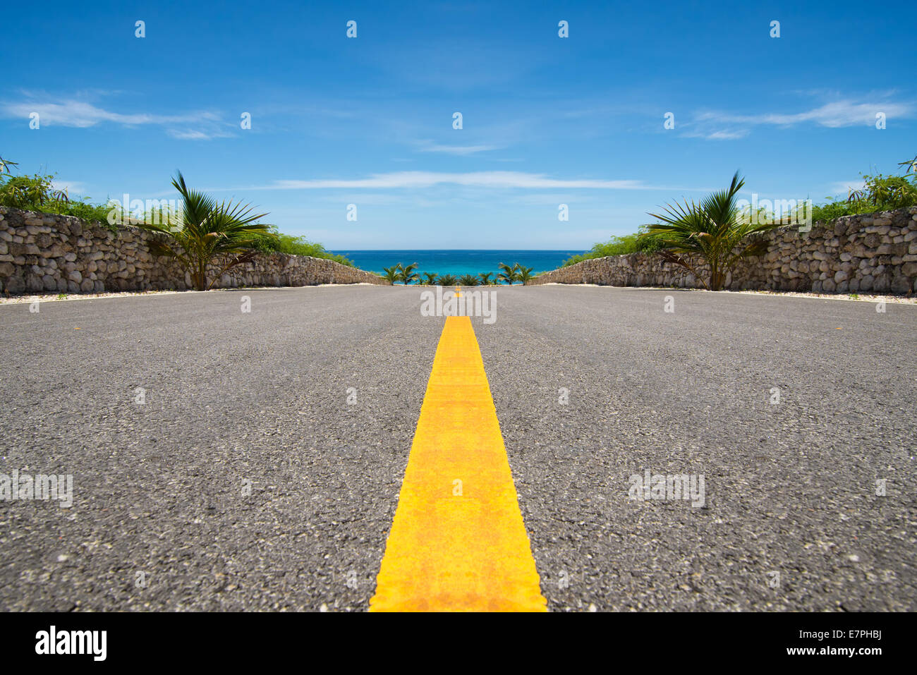Road with yellow line ending in tropical sea, ocean - Stock Image