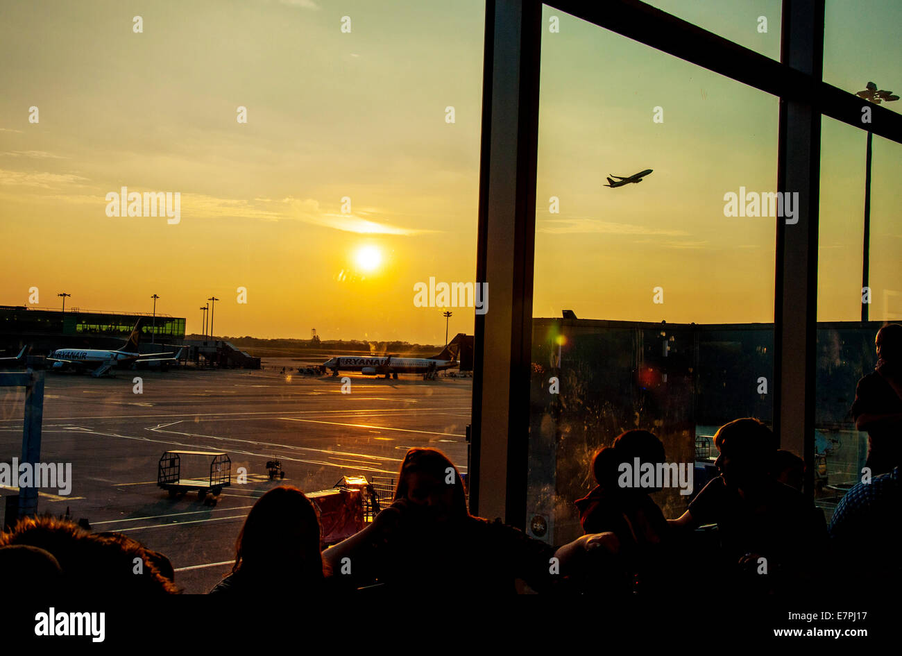 Stansted Airport UK.  Pasengers waiting in departure lounge at sunset. On-time performance of scheduled flights - Stock Image