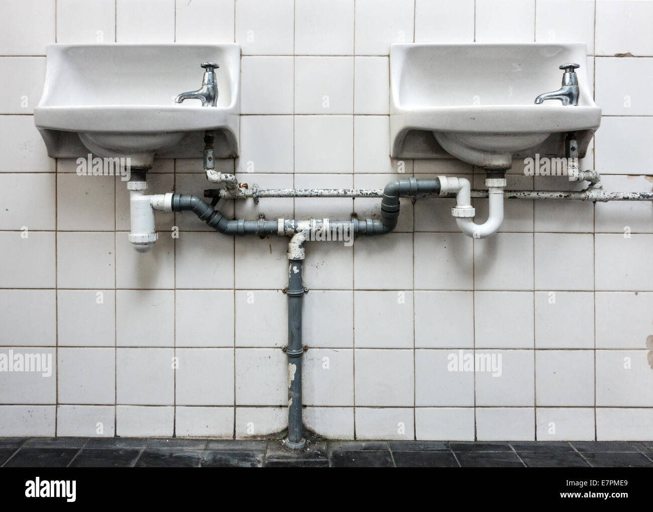 Twin hand washing sinks and plumbing in an Edwardian Grade II listed lavatory building in central Bristol UK - Stock Image