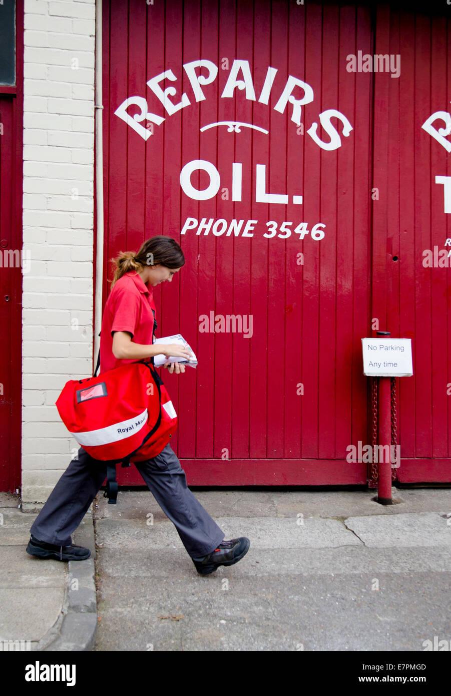 Post woman in red walking past red garage doors in Clifton Bristol UK - Stock Image