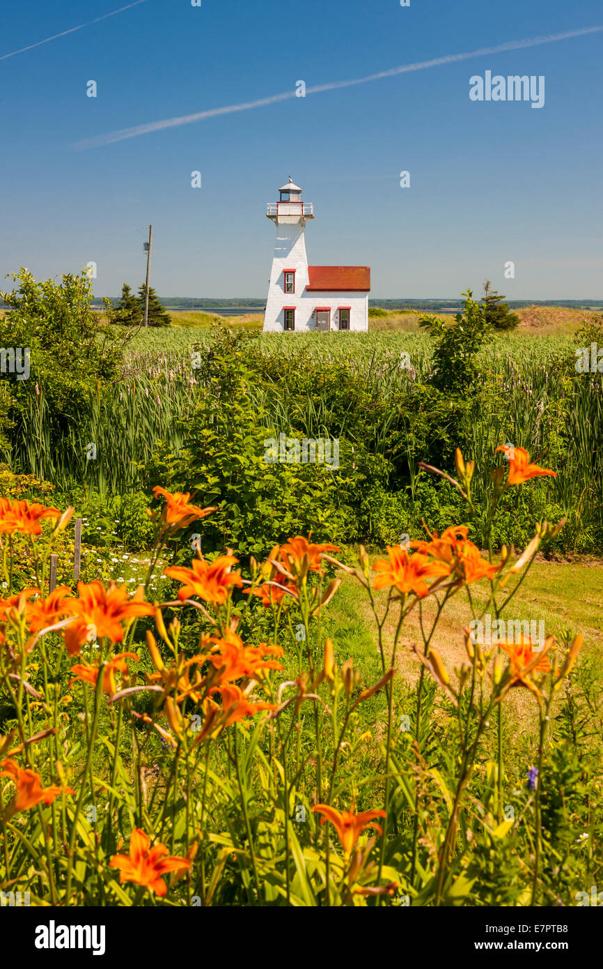 New London Range Rear Lighthouse with orange lilies in Queens County, Prince Edward Island, Canada. - Stock Image