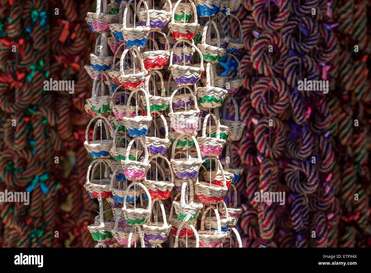 Tiny decorative baskets made of straw hang outside a market in Tzintzuntzan, Michoacan, Mexico. - Stock Image