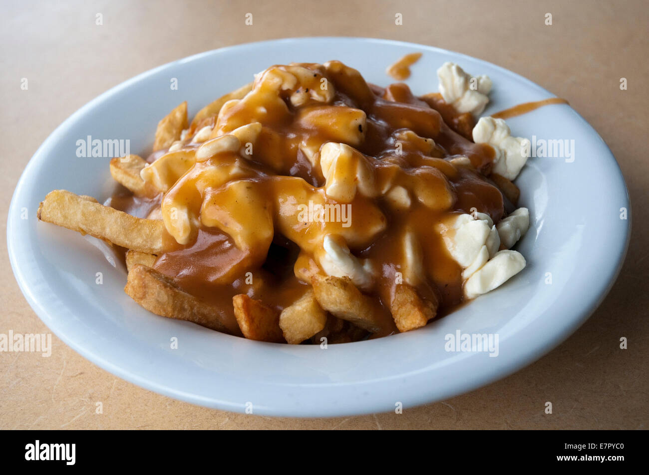 The famous 'traditional' poutine at Le Roy Jucep restaurant in Drummondville, Quebec, Canada. - Stock Image