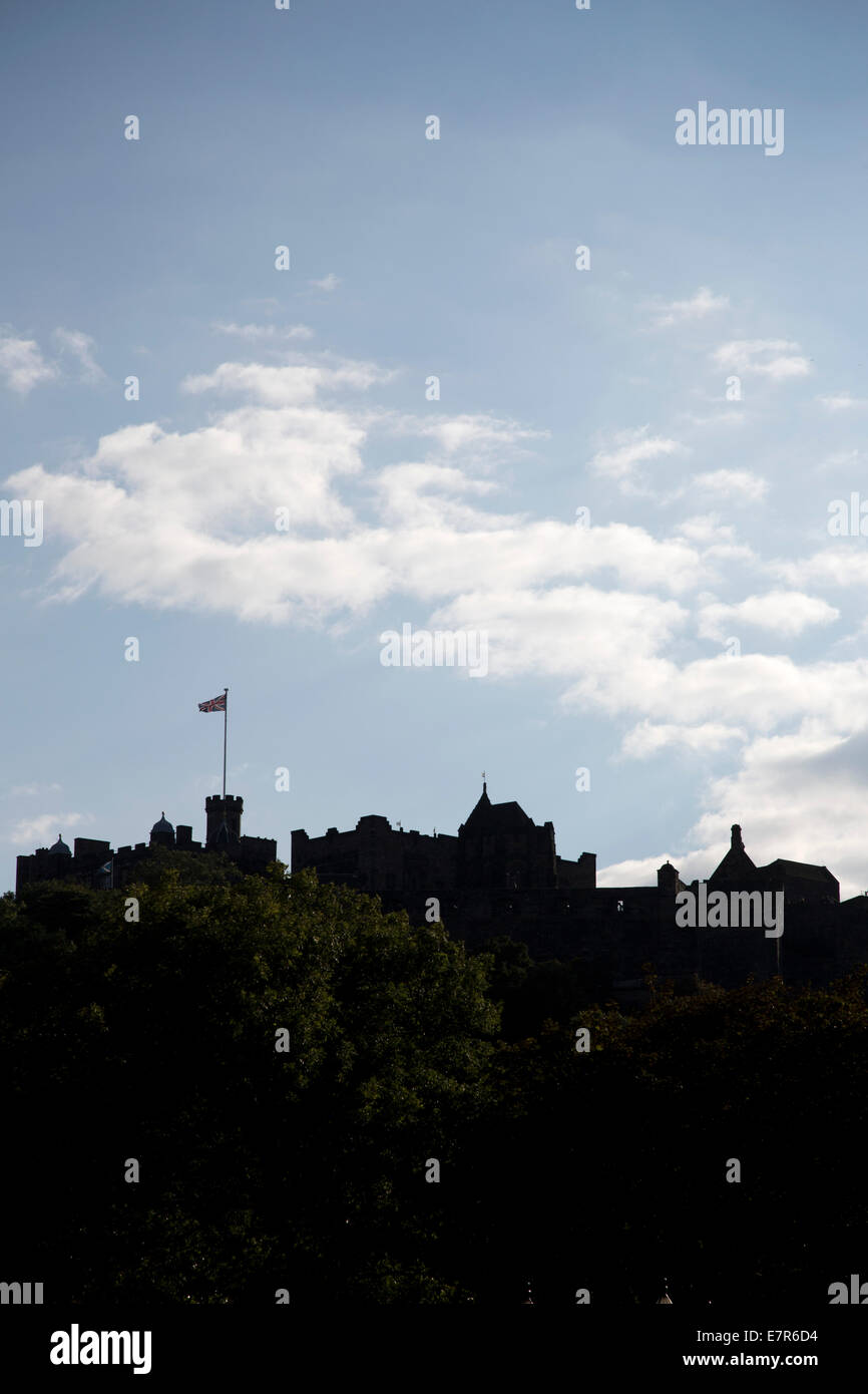 A silhouette of Edinburgh castle with the Union Jack flag flying on top of it. - Stock Image