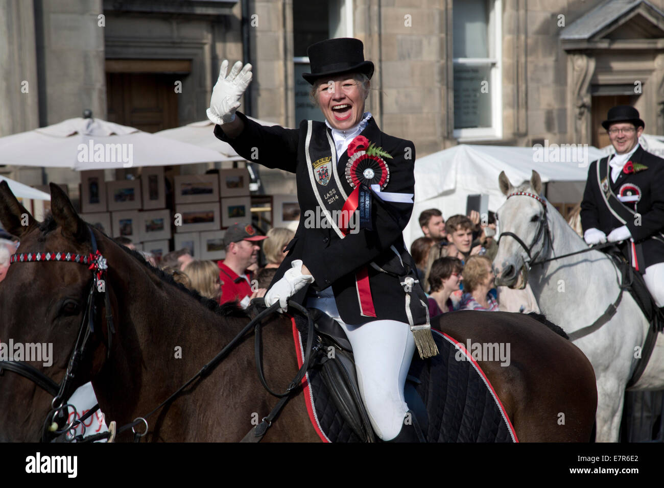 A woman on a horse waving to people in the crowd on the Royal Mile, Edinburgh before the annual Riding of the Marches - Stock Image