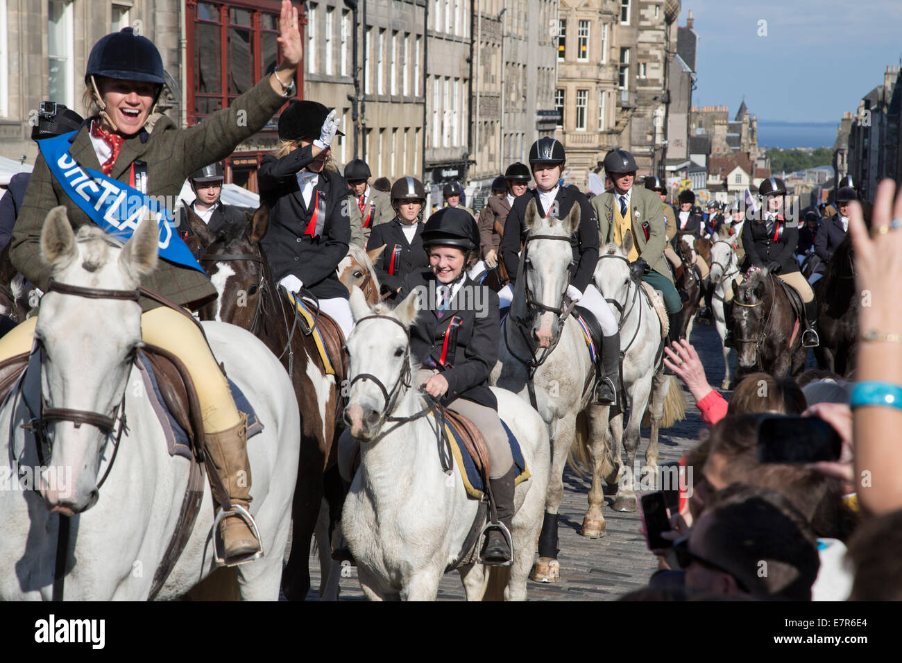 A woman on a horse waving to people in the crowd on the Royal Mile, Edinburgh before the annual Riding of the Marches Stock Photo
