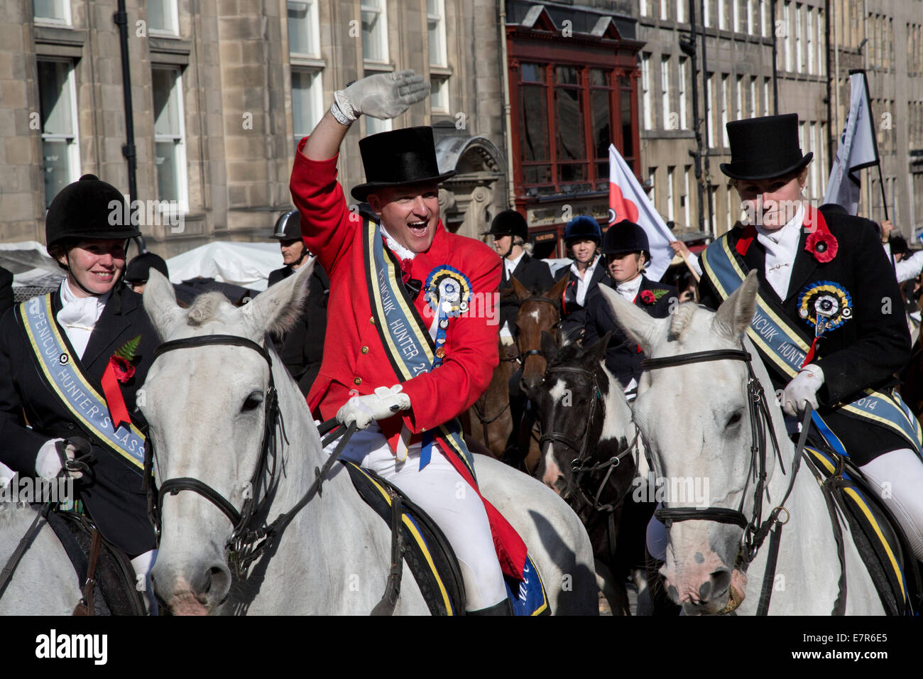A man on a horse waving to people in the crowd on the Royal Mile in Edinburgh before the annual Riding of the Marches - Stock Image