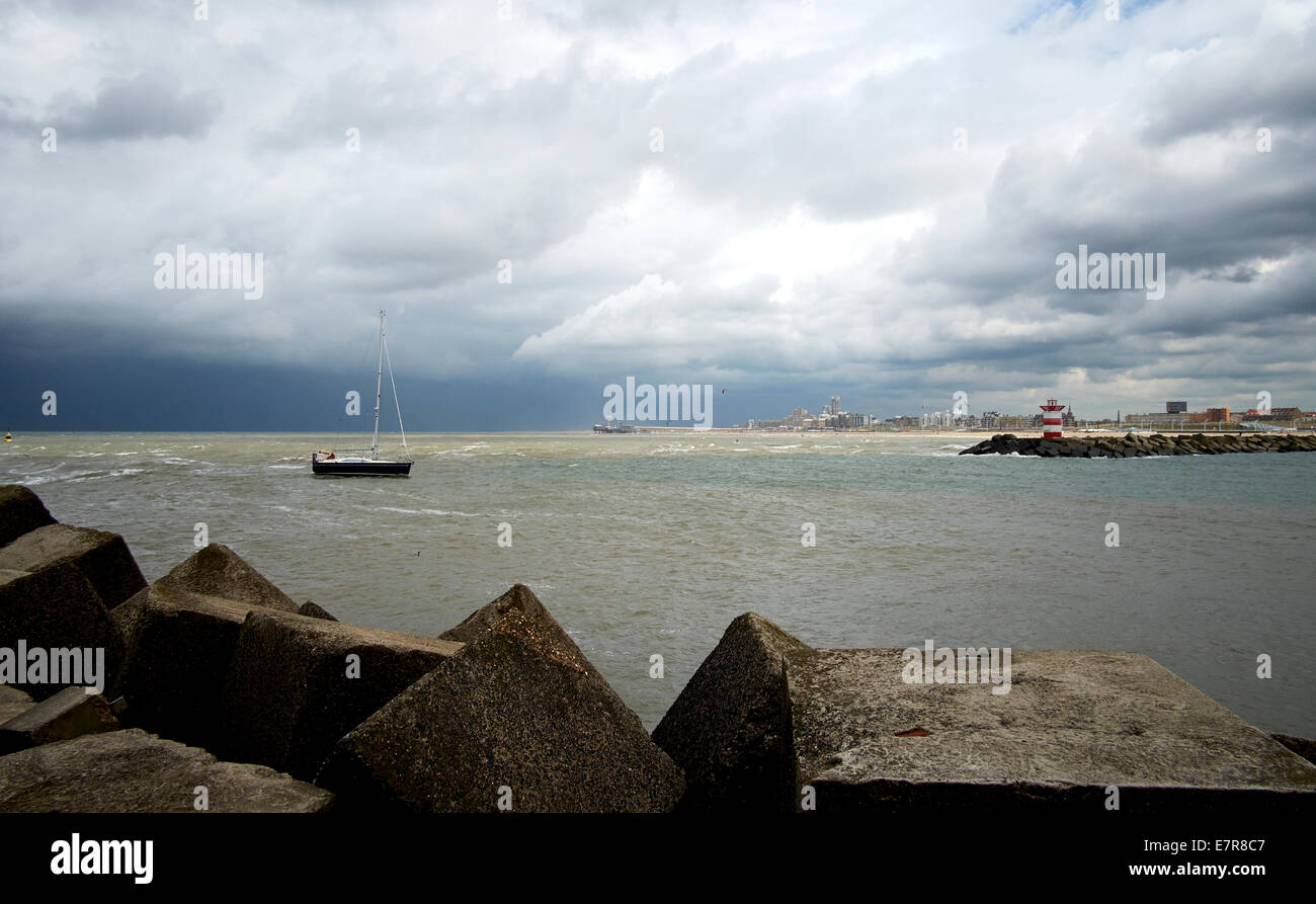 Boat is navigating between jetty harbours at the entrance of the port of Scheveningen followed by bad weather. - Stock Image