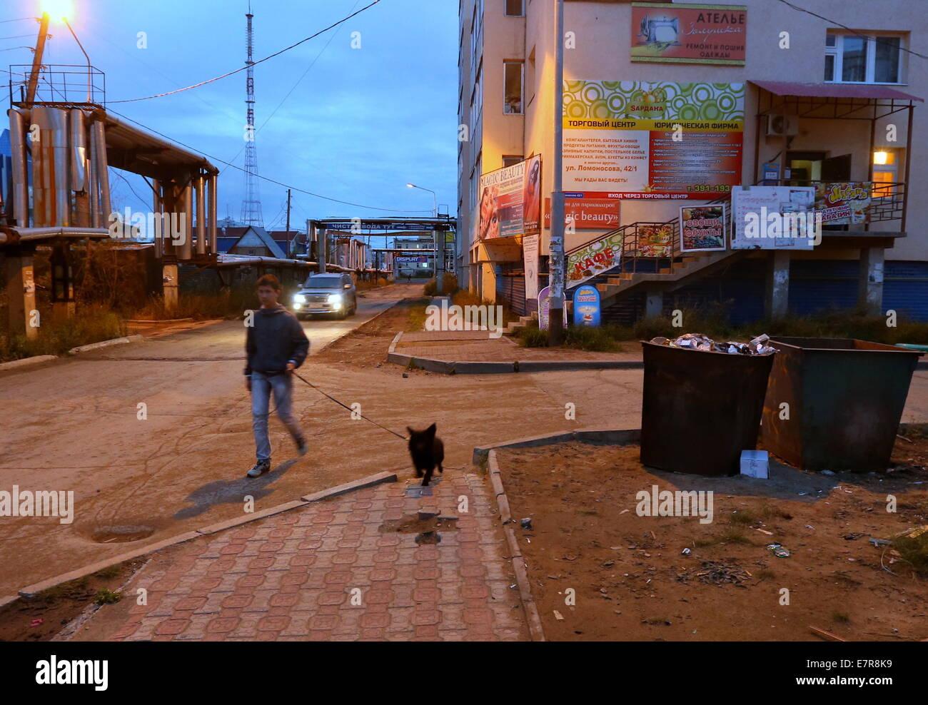 Yakutsk, Russia. 23rd Sep, 2014. A man walking his dog. © Valery Sharifulin/ITAR-TASS/Alamy Live News - Stock Image
