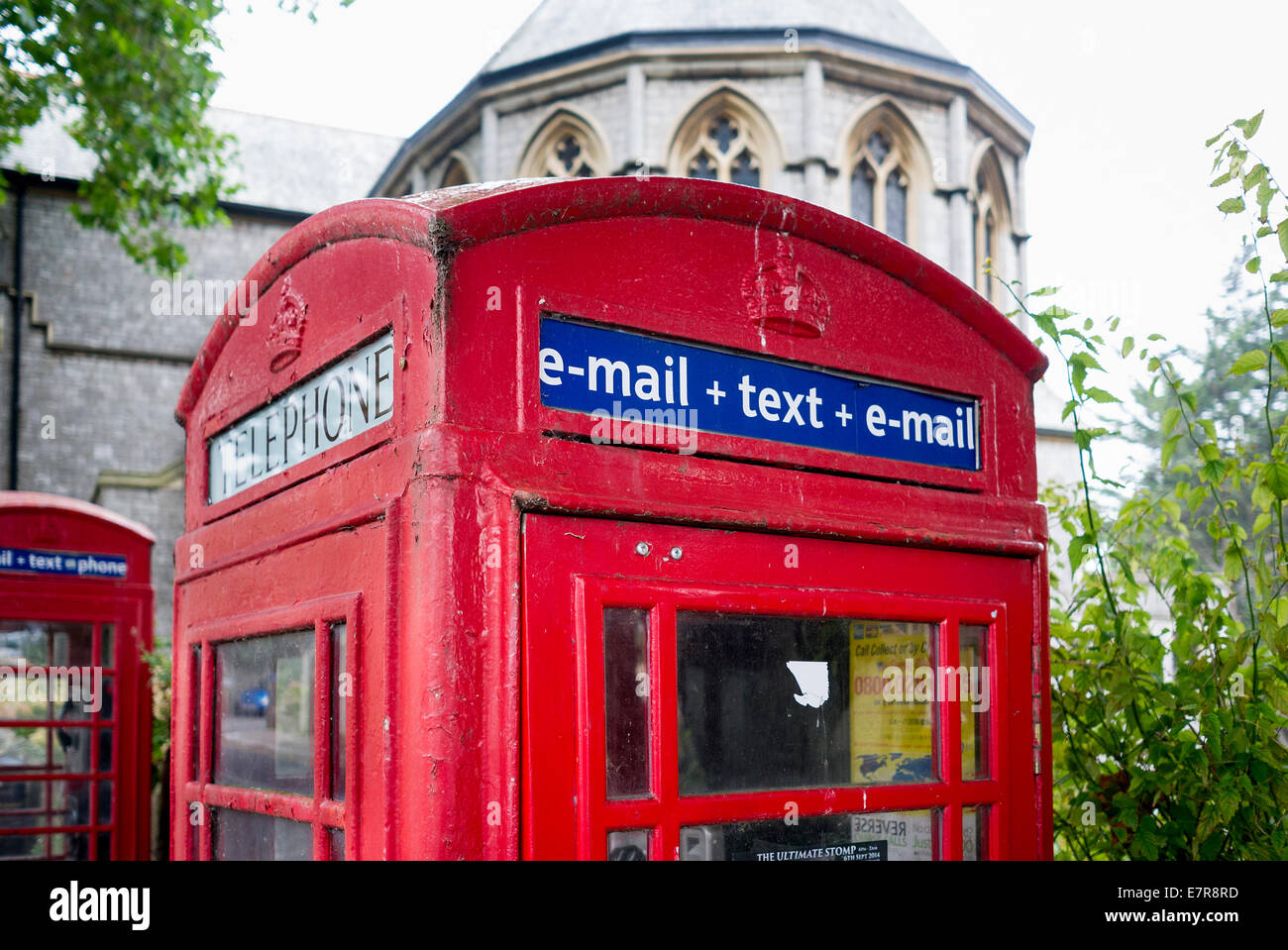 Classic red post office telephone box showing modern services including e-mail and text messaging - Stock Image