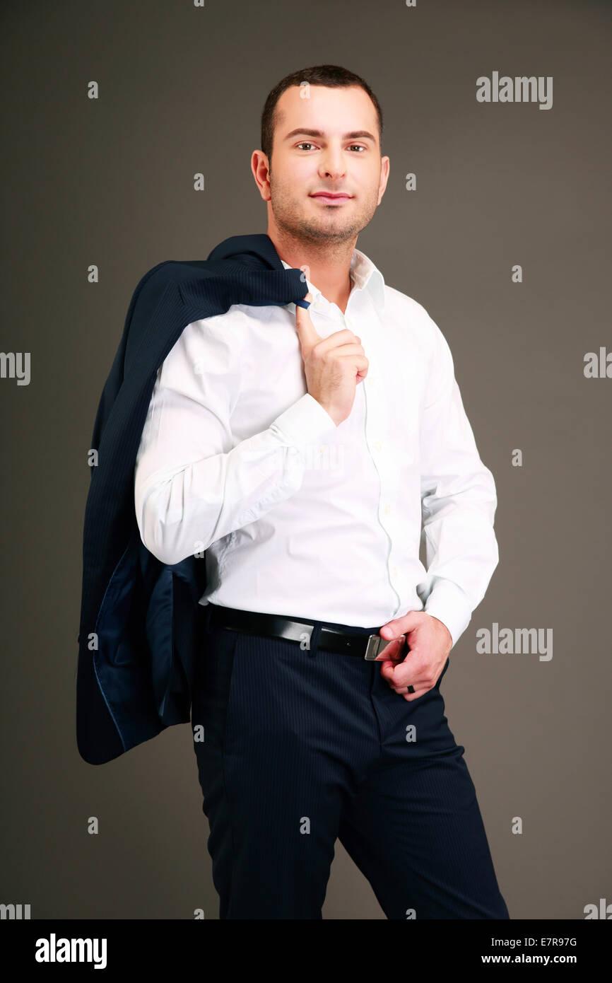 Handsome businessman holding his jacket over shoulder on gray background Stock Photo