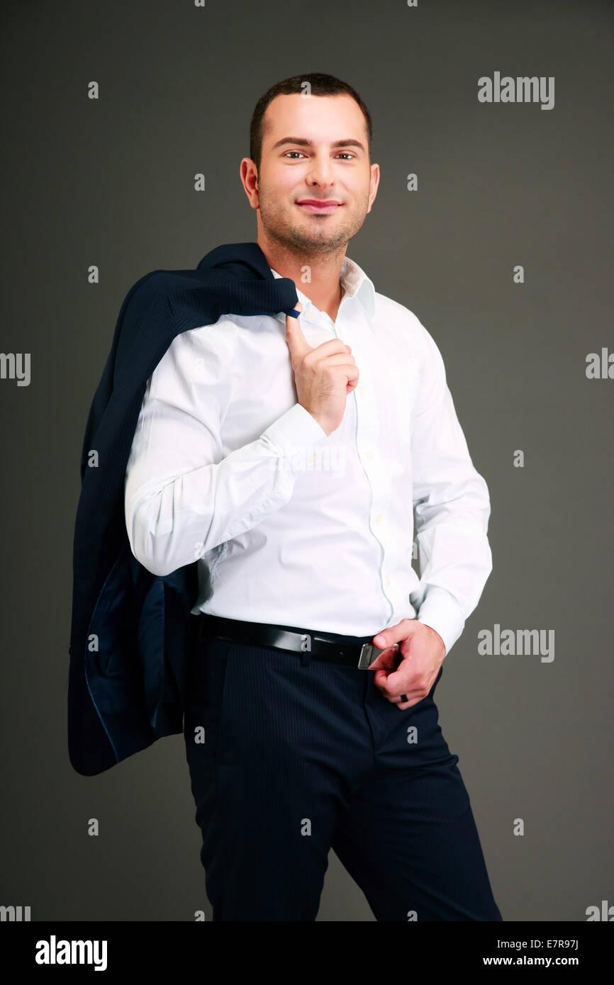 Portrait of a businessman holding his jacket over shoulder - Stock Image