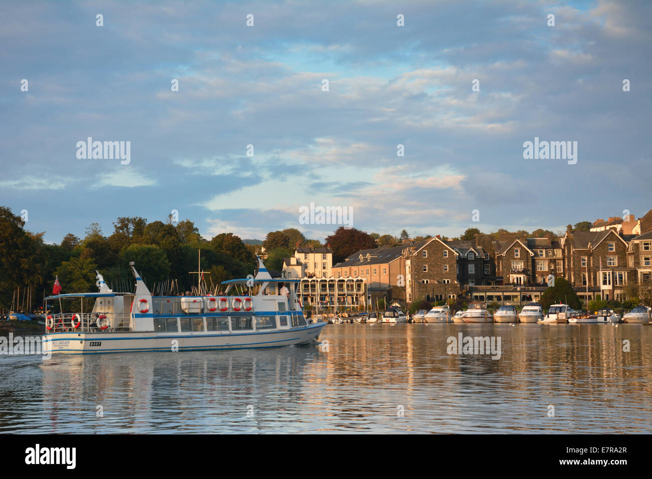A Windermere cruiser entering Bowness in the early evening sunlight - Stock Image