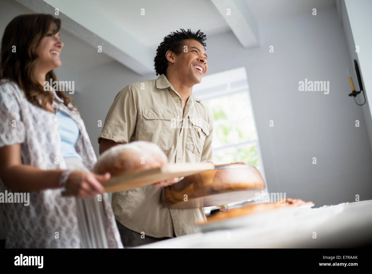 A family gathering for a meal. Food being carried to a table. - Stock Image