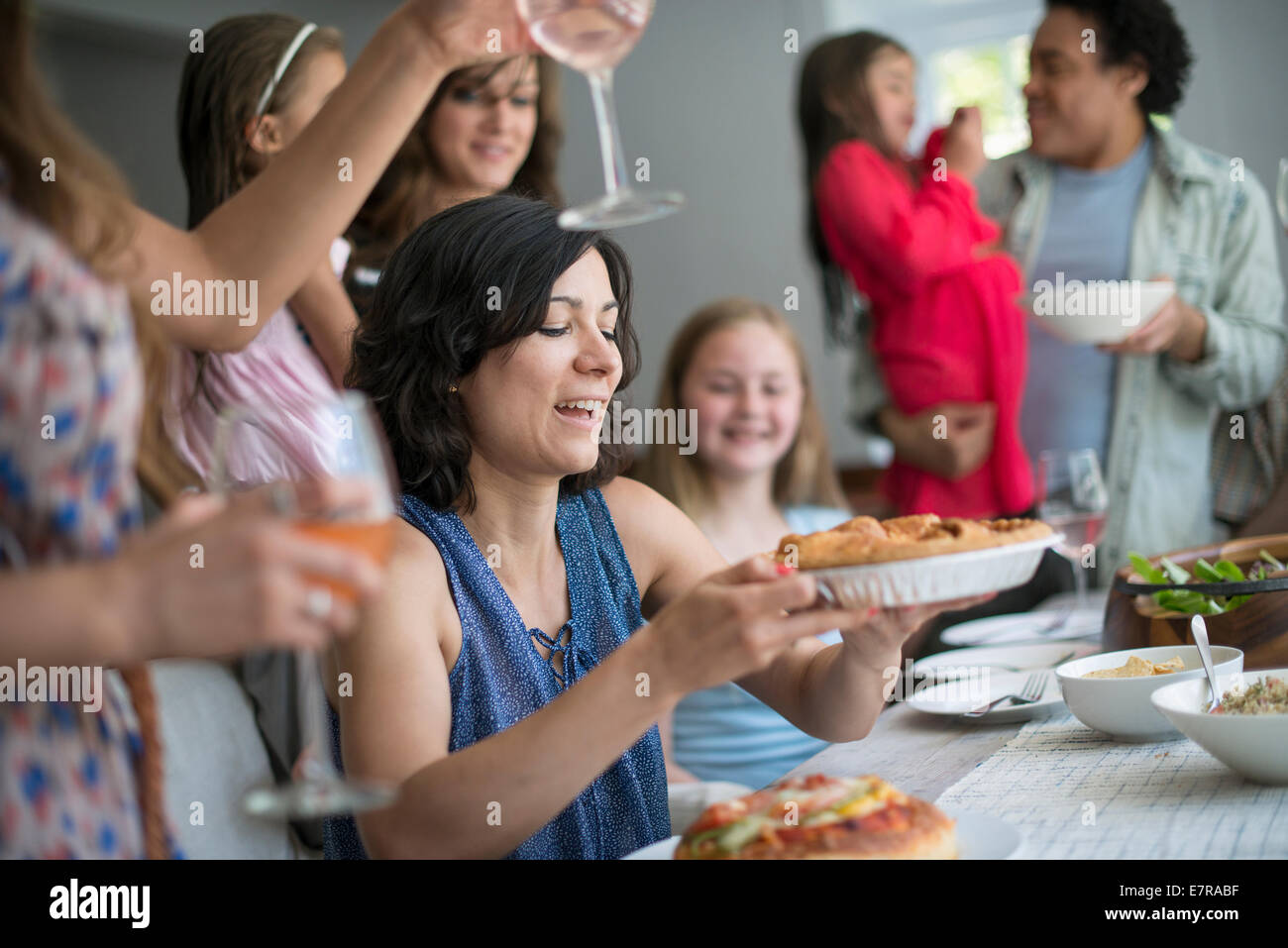 A family gathering for a meal. Adults and children around a table. - Stock Image