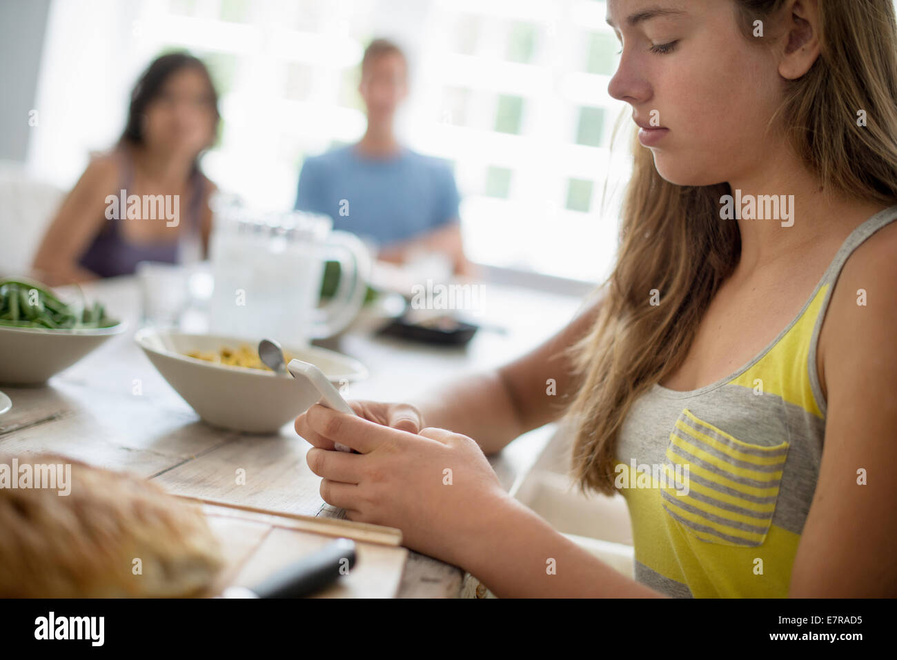 A young girl seated checking her smart phone at a dining table. Two people in the background. Stock Photo