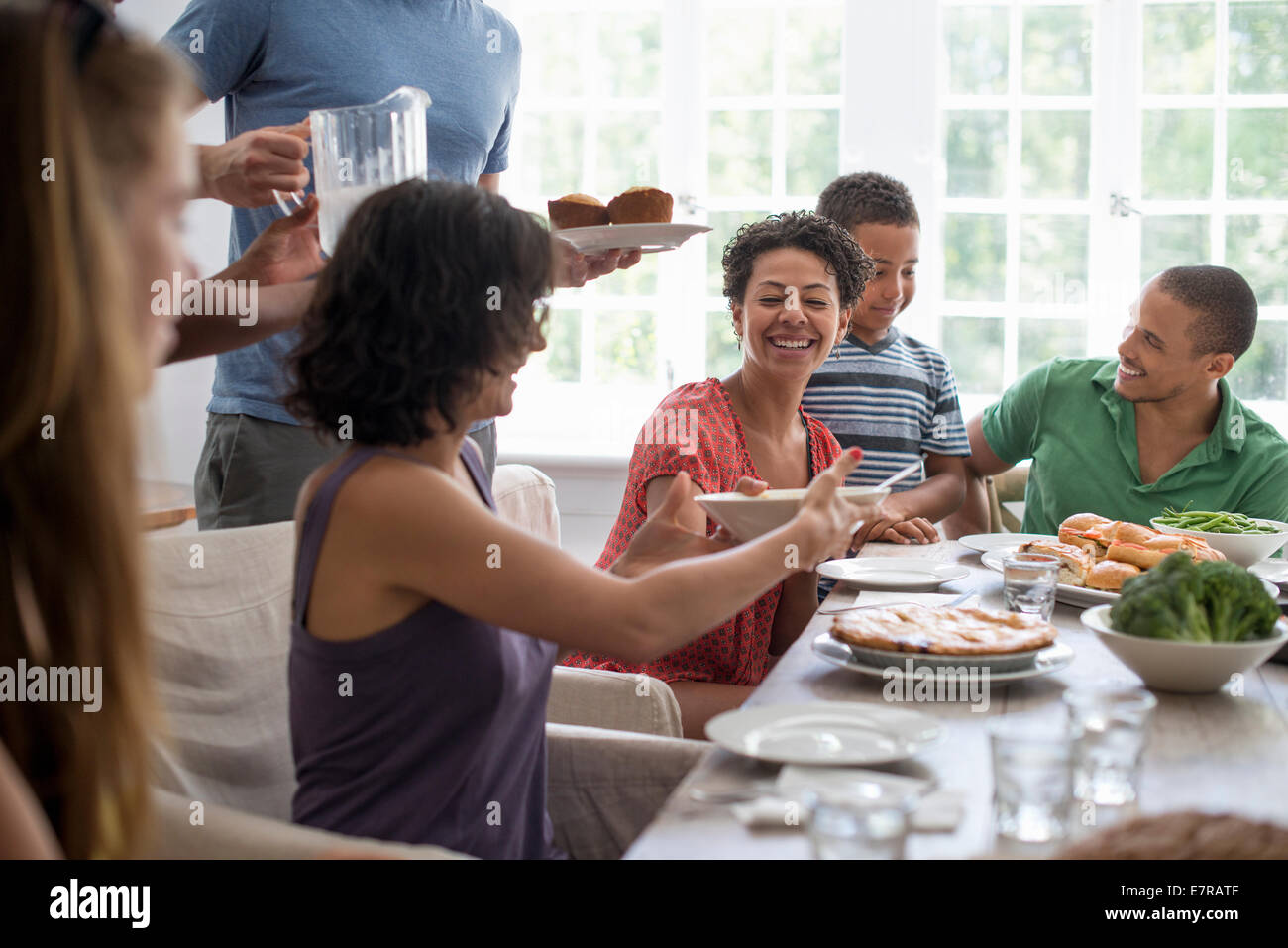 A family gathering, men, women and children around a dining table sharing a meal. - Stock Image