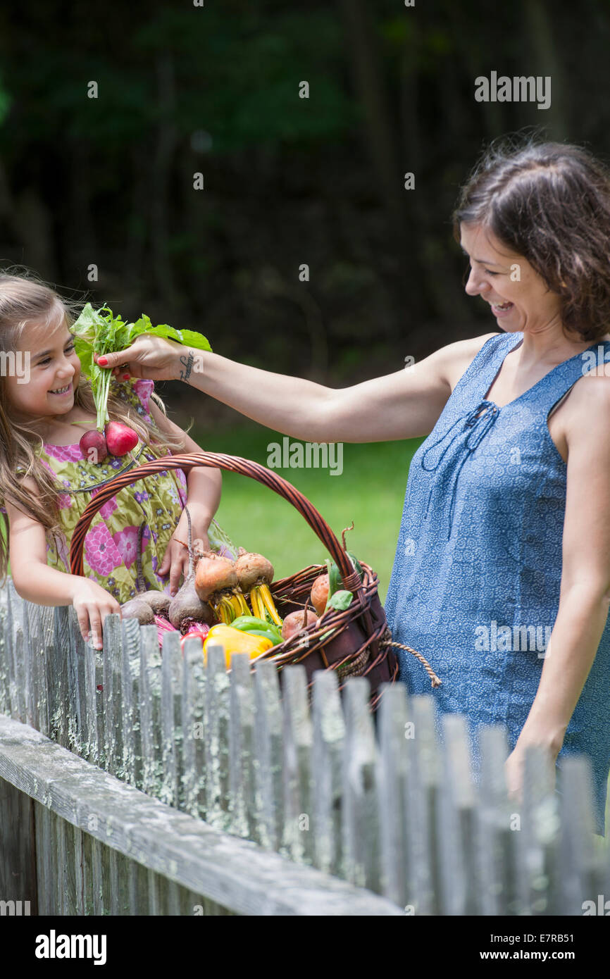 Mother and daughter standing in a garden with a basket of vegetables. - Stock Image