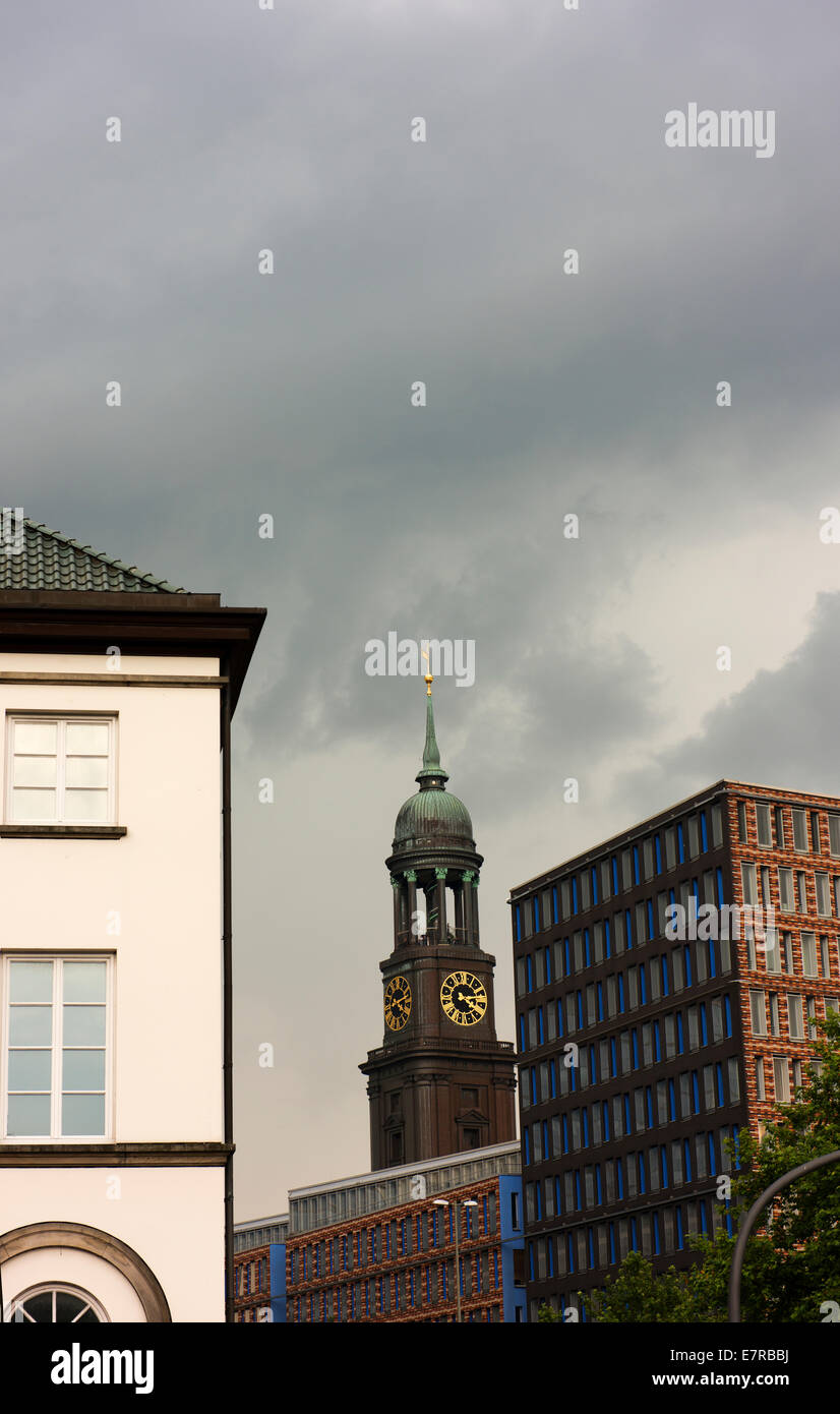Spire of St Michael's Church with other city buildings on an overcast winter day. - Stock Image