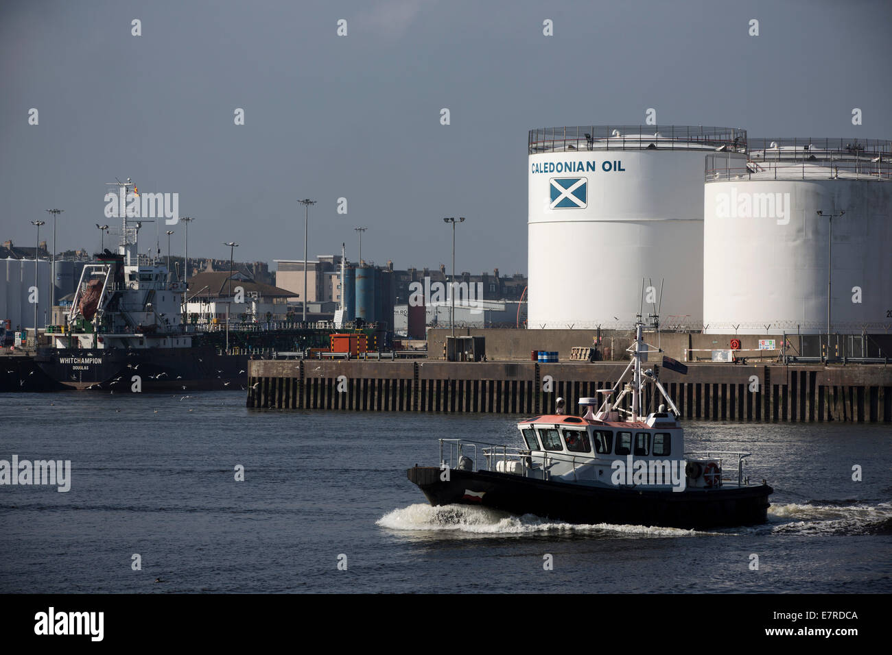 A tug boat crosses the mouth of Aberdeen harbour, the Scotland's North Sea oil and gas transportation and maintenance - Stock Image