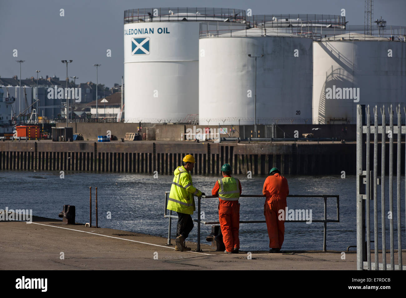 Three work men standing on one of the quay's at Aberdeen harbour, the Scotland's North Sea oil and gas transportation - Stock Image