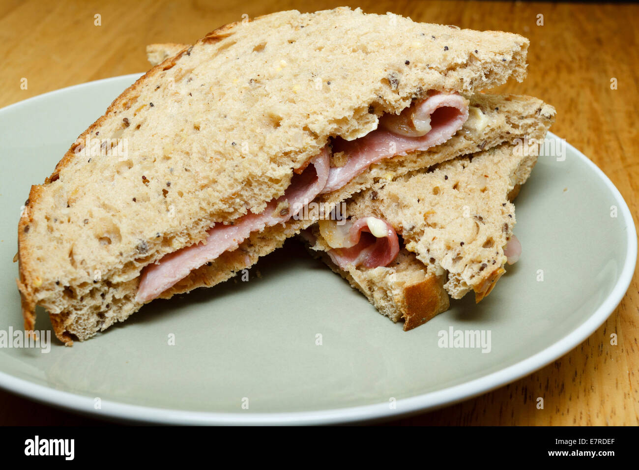 Bacon sandwich on seeded bread, cut into halfs as triangles - Stock Image