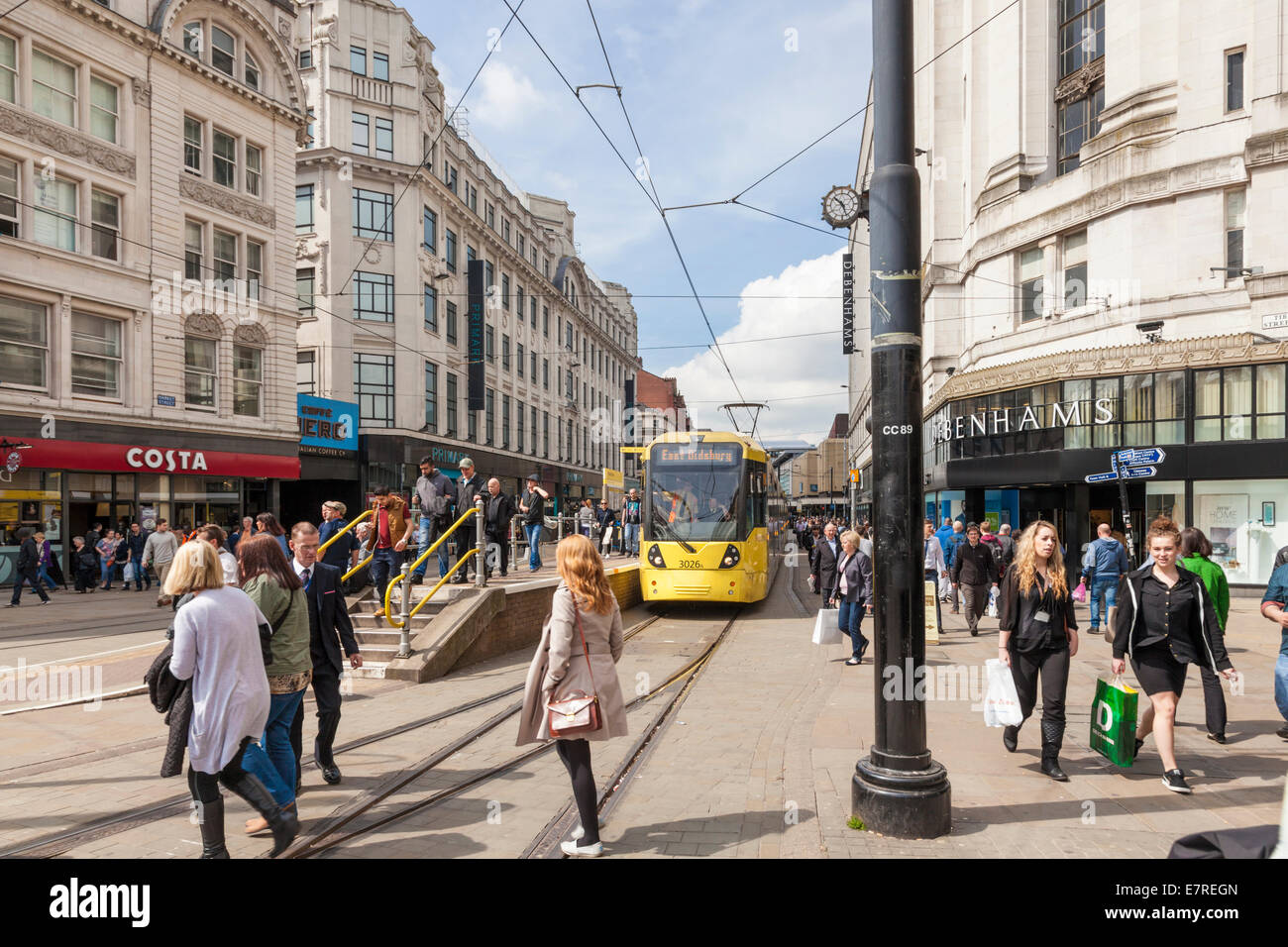People shopping and a Metrolink tram on the busy Market Street in Manchester city centre, England, UK - Stock Image