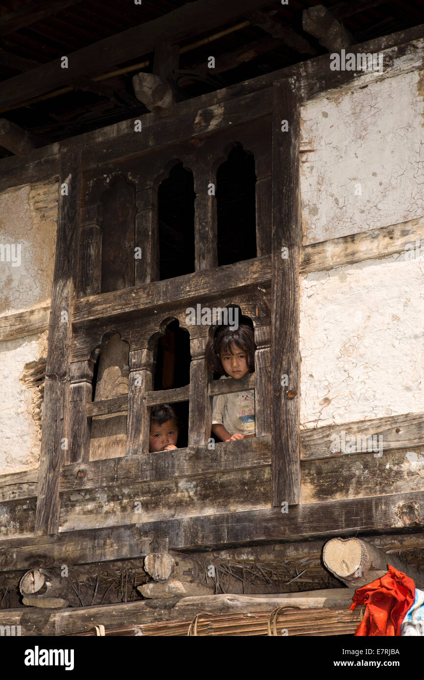 Eastern Bhutan, Trashi Yangtse, children looking through traditional wooden farmhouse window - Stock Image