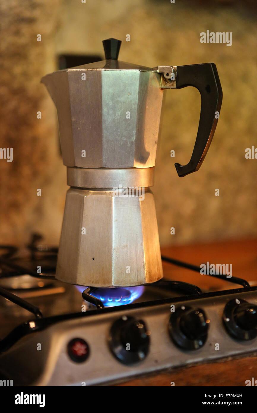 Moka pot brewing coffee on a stove - Stock Image