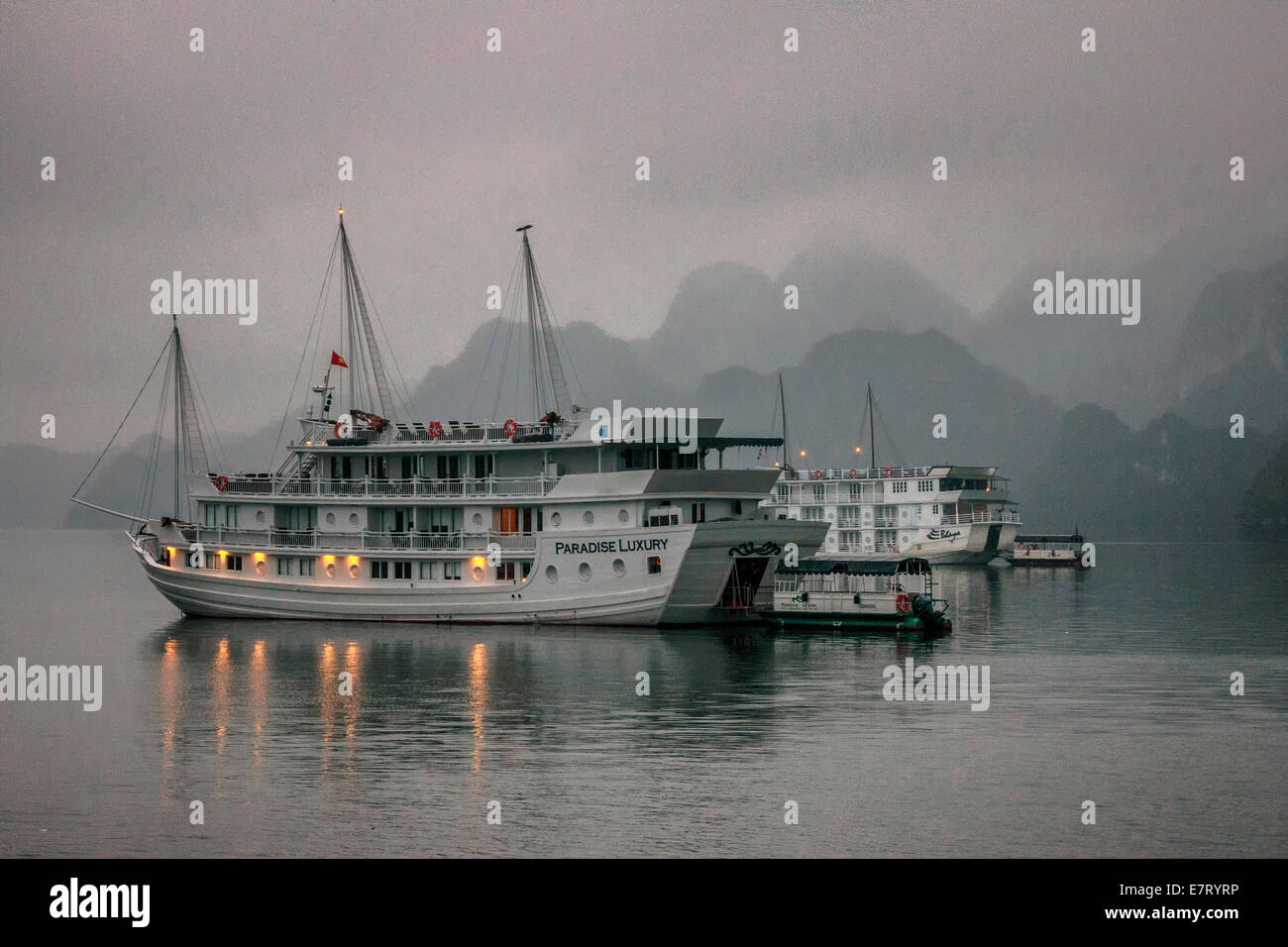 Cruise junk boat sits under early morning fog in front of limestone mountains. - Stock Image