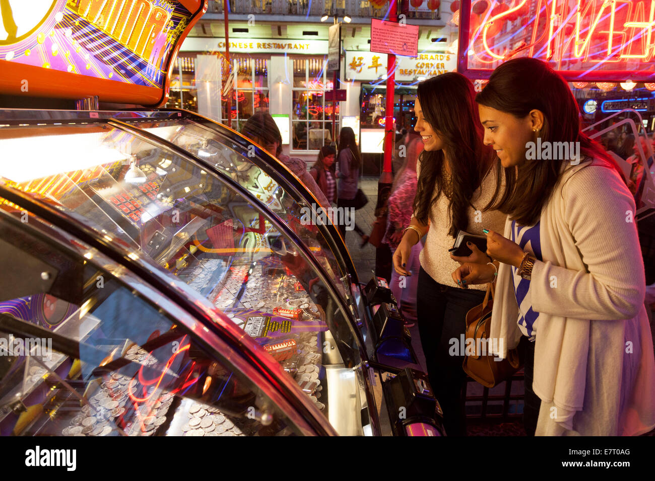 Two women playing gambling games in an amusement arcade, Soho, London UK - Stock Image