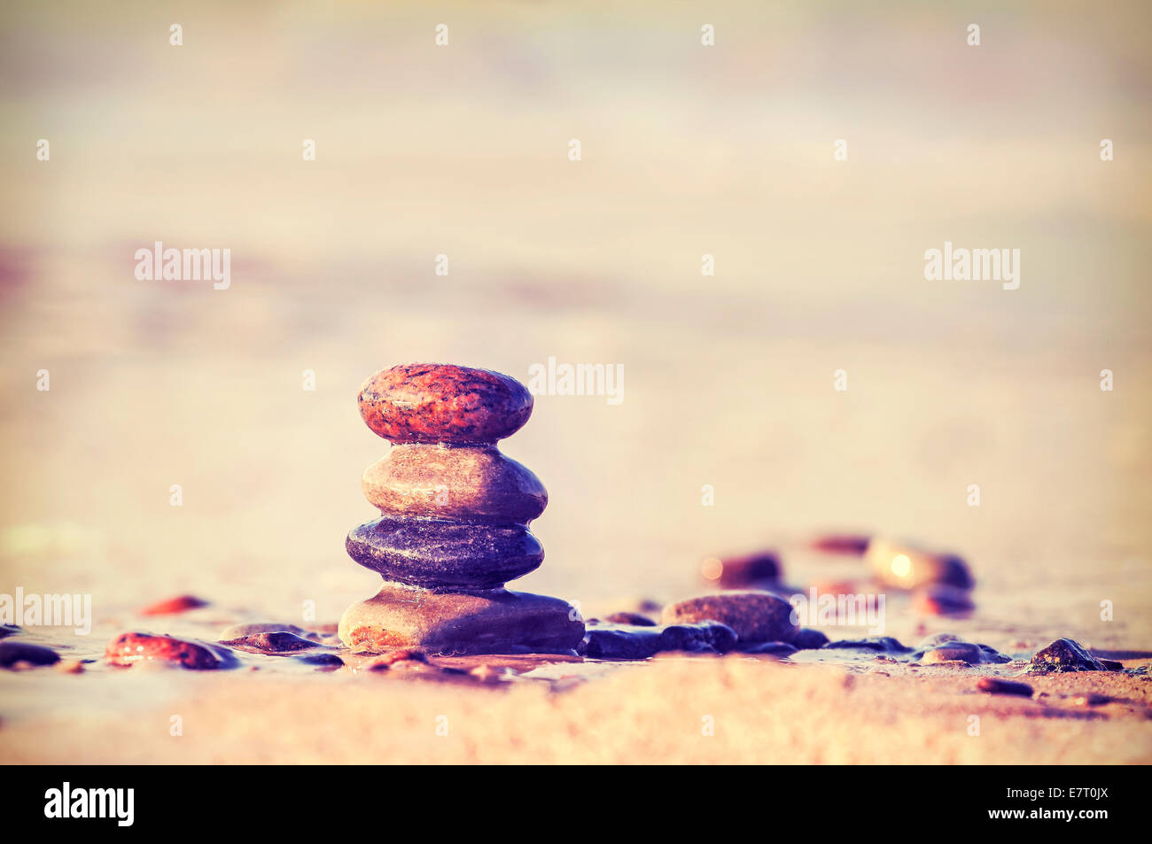 Vintage retro style image of stones on beach. - Stock Image