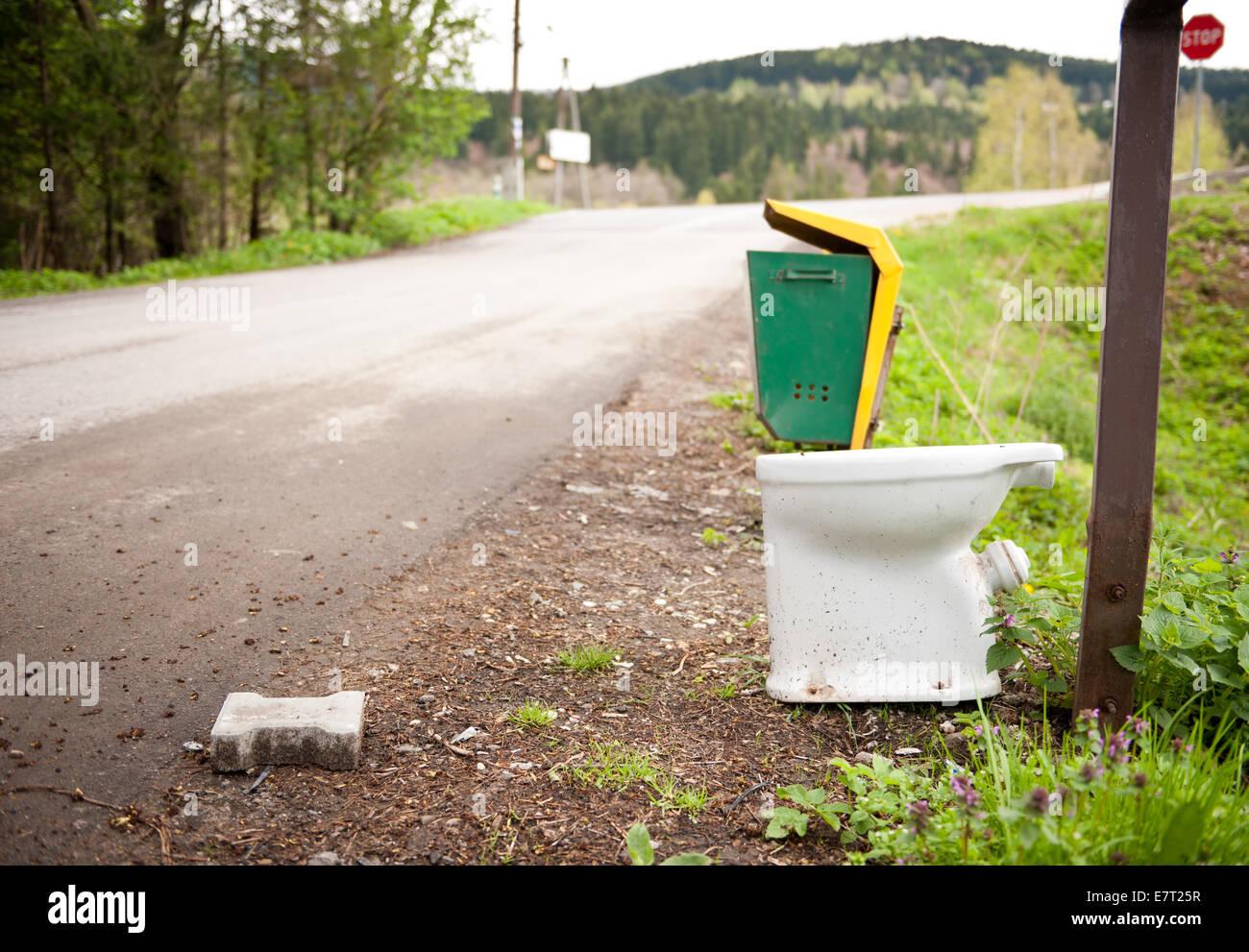 Old used toilette roadside garbage thrown away - Stock Image